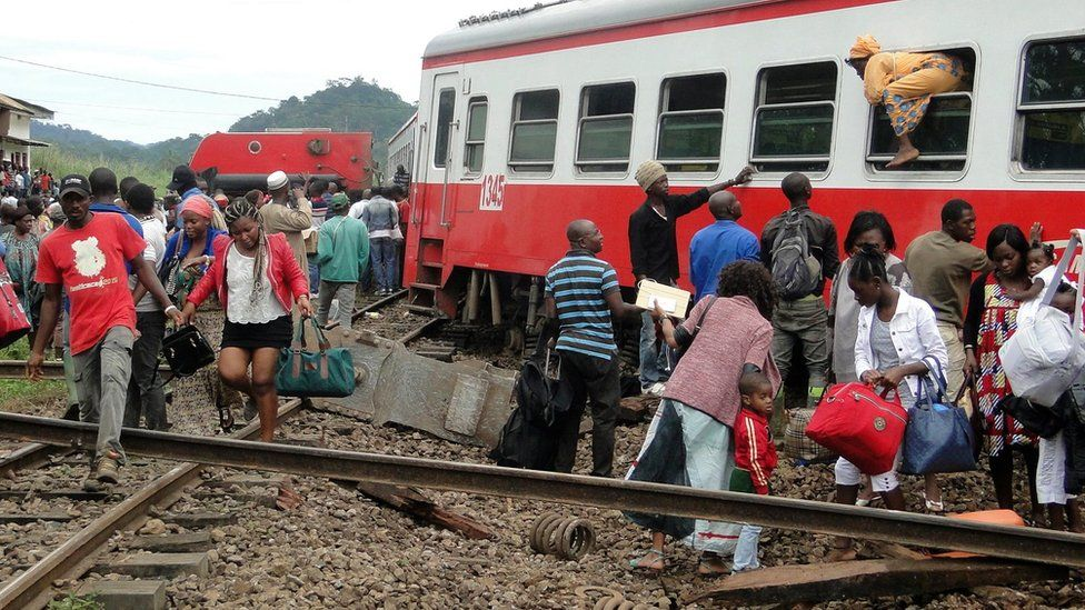 A passenger escapes a train car using a window as others leave from the site of a train derailment in Eseka on October 21, 2016.