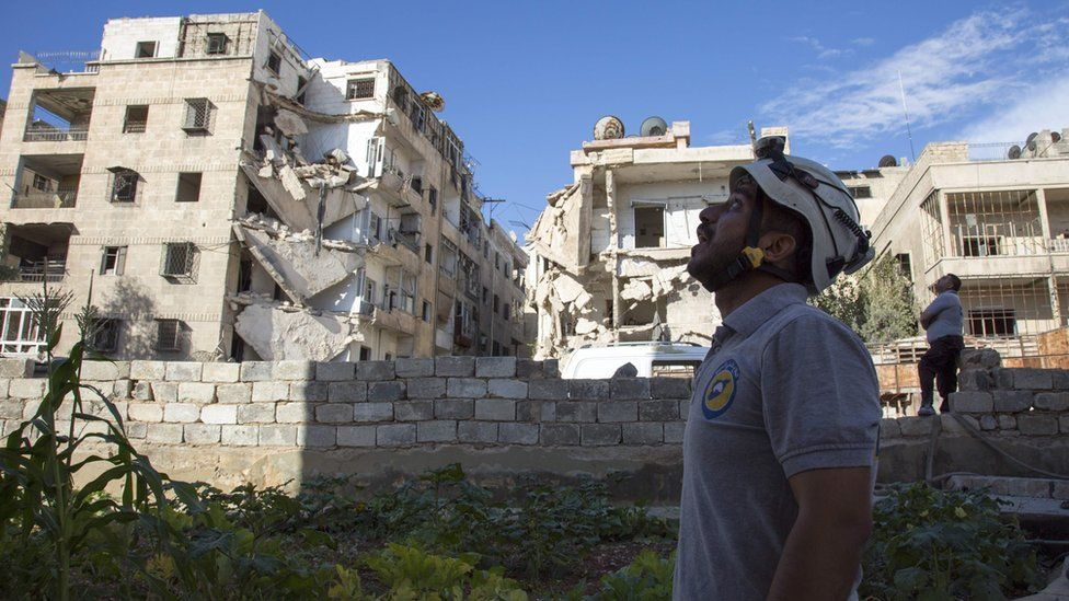 A Syrian rescuer looks towards the sky following an air strike in the rebel-held Ansari district in the northern Syrian city of Aleppo on September 23, 2016.