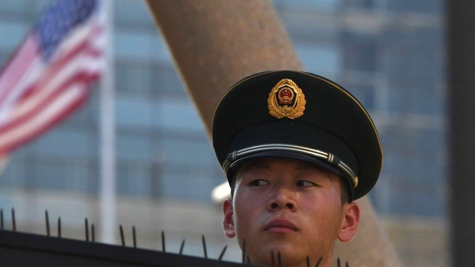 A paramilitary policeman looks on past the US flag on the embassy compounds in Beijing