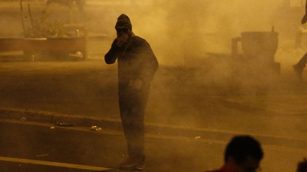 A man covers his mouth with a scarf in thick tear gas, September 4