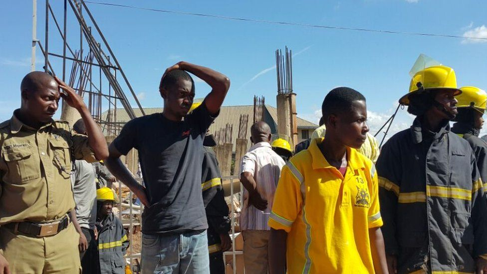 emergency workers and site workers look on at the scene of the collapse