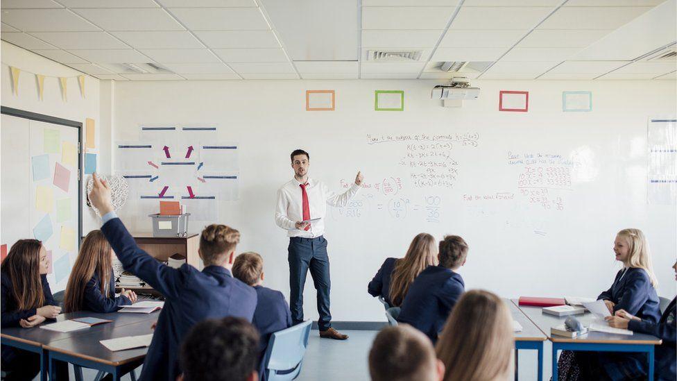 A maths teacher in front of a class