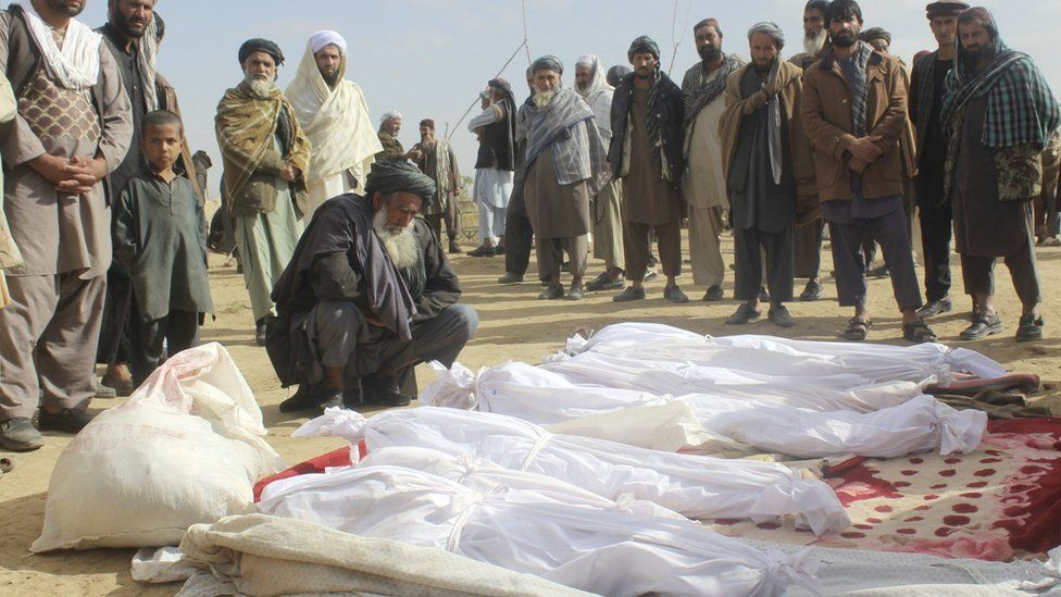 In this 4 November 2016 photo, Afghan villagers gather around several victims' bodies who were killed during clashes between Taliban and Afghan security forces in the Taliban-controlled, Buz-e Kandahari village in Kunduz province, Afghanistan