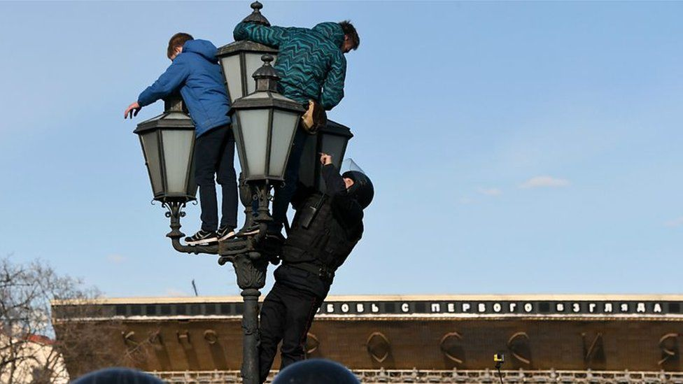 Teenagers climbing a lamp post at a protest in Moscow in March