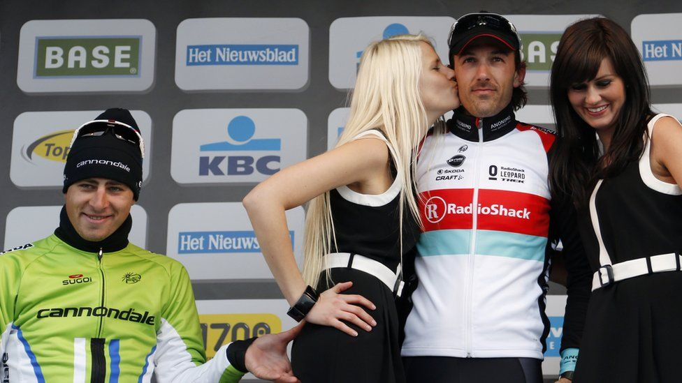 Peter Sagan pinching a podium girl's bottom on the winner's podium, with Fabio Cancellara and two podium girls in the picture