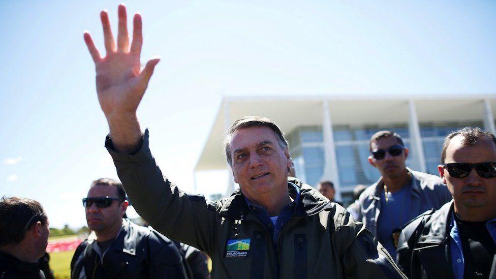 Brazil's President Jair Bolsonaro gestures to the crowd at a motorcade rally