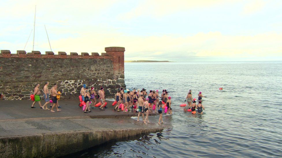 Swimmers heading into water off the County Down coast
