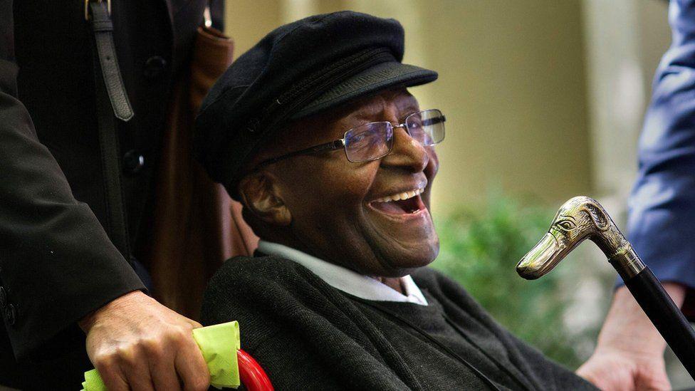 Desmond Tutu smiles in a wheelchair