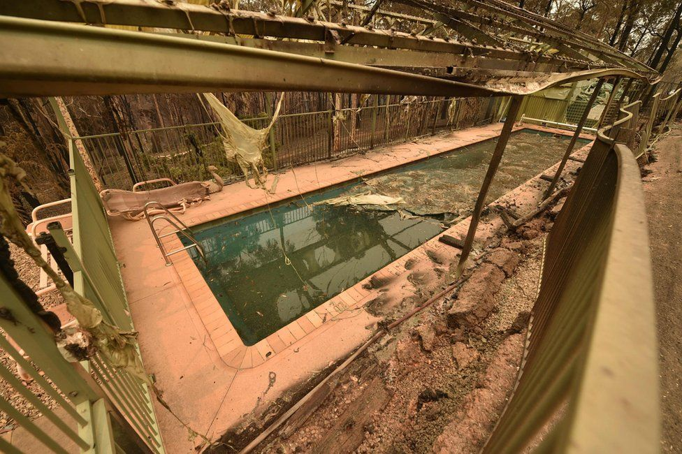 Debris seen around a swimming pool next to the remains of a house destroyed by bushfires