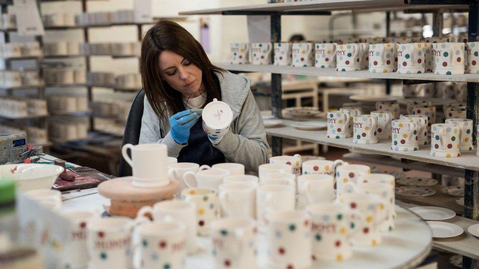 A worker hand-paints crockery in a factory