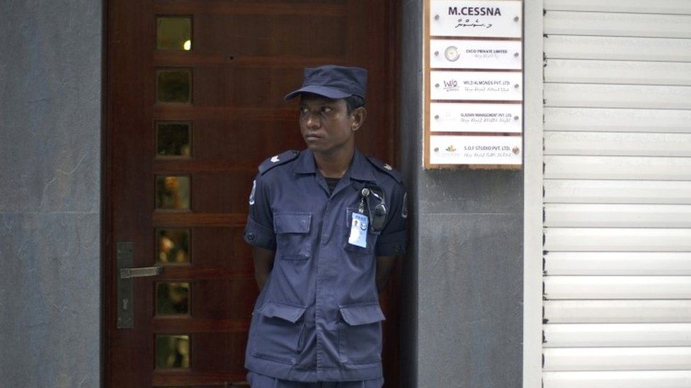 A Maldives police officer stands guard outside the residence of former Vice President Mohamed Jameel in Male (24 October 2015)