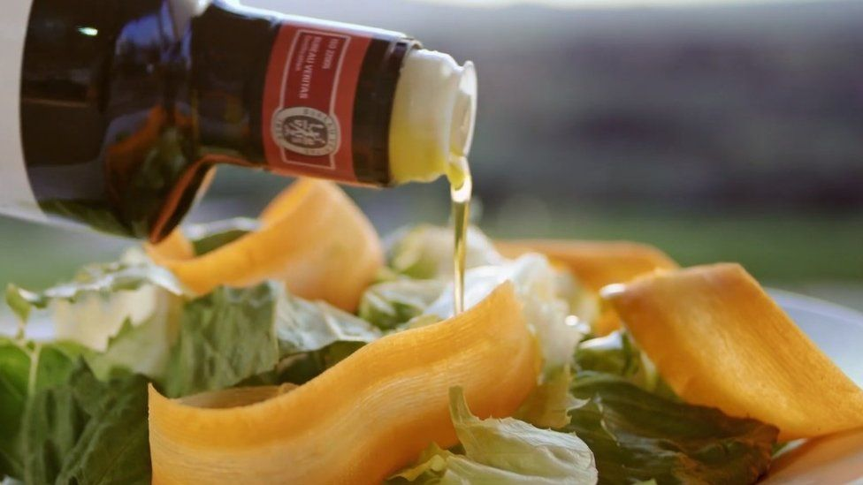 Olive oil being poured over salad
