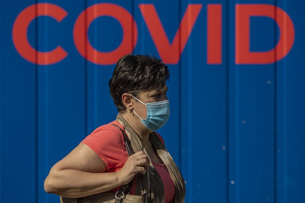 A woman wearing protective face mask walks in front of a coronavirus testing station