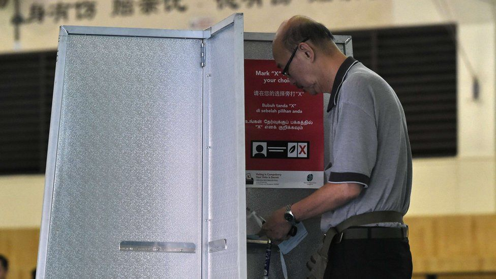 A Singaporean man casts his vote at a polling station in Singapore on 11 September 2015