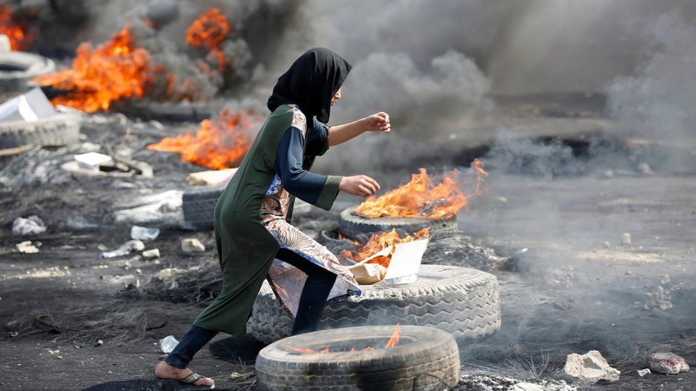 A protester runs between burning tyres in Baghdad, Iraq (3 October 2019)