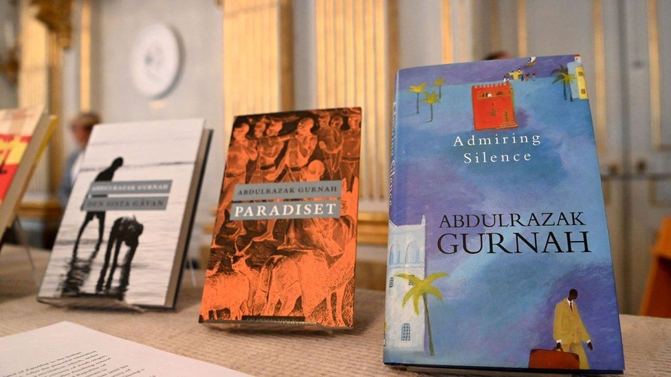 Three books are in view, they include the titles: Admiring Silence and Paradiset. The books are displayed on a table