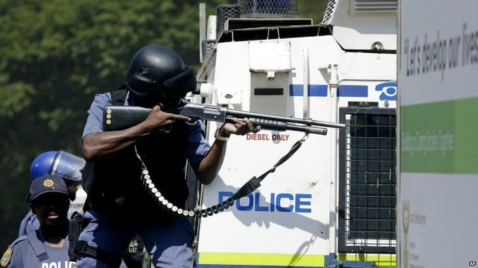 Riot police officer aims at protesters during the march against university tuition hikes outside the union building in Pretoria, South Africa,