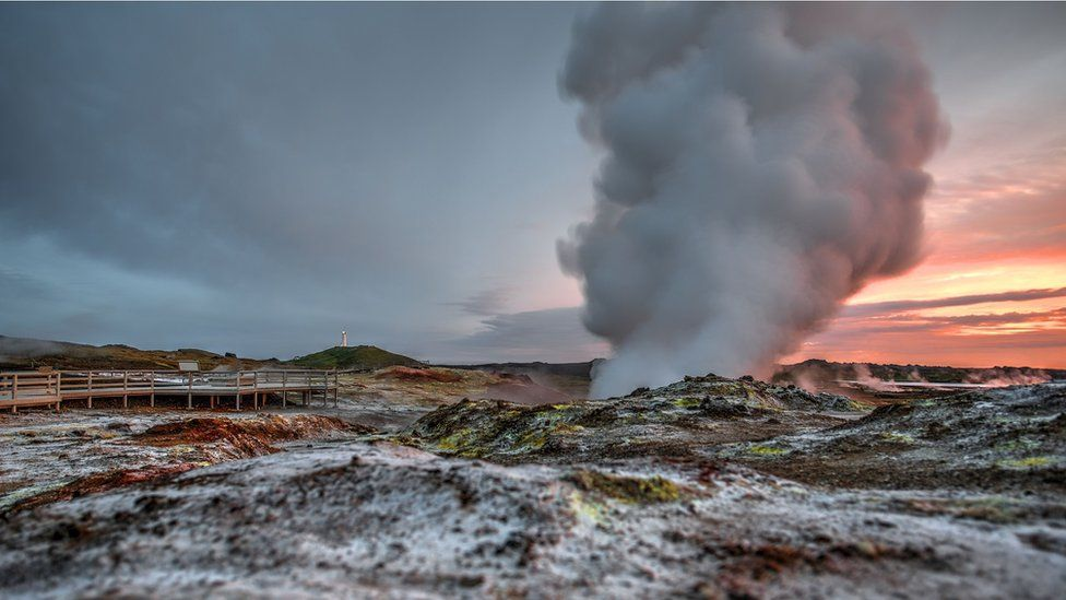 Steam emerges from a geothermal vent, a sunset in the background