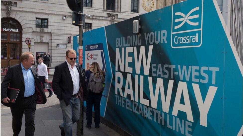 People walk past billboards promoting Crossrail's new Queen Elizabeth rail line in Moorgate, London