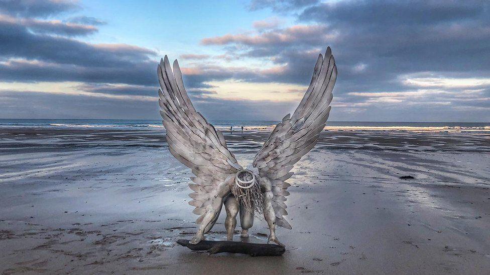 Angel statue on beach.