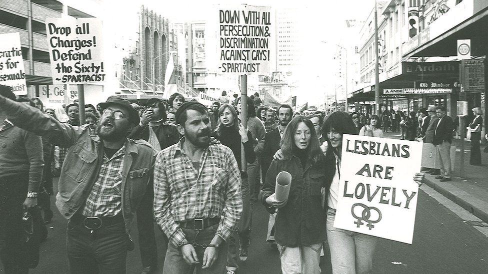 """Marchers in the 1978 Mardi Gras and Gay Solidarity Group protests hold placards including """"lesbians are lovely"""" and """"down with all persecution and discrimination against gays!"""""""