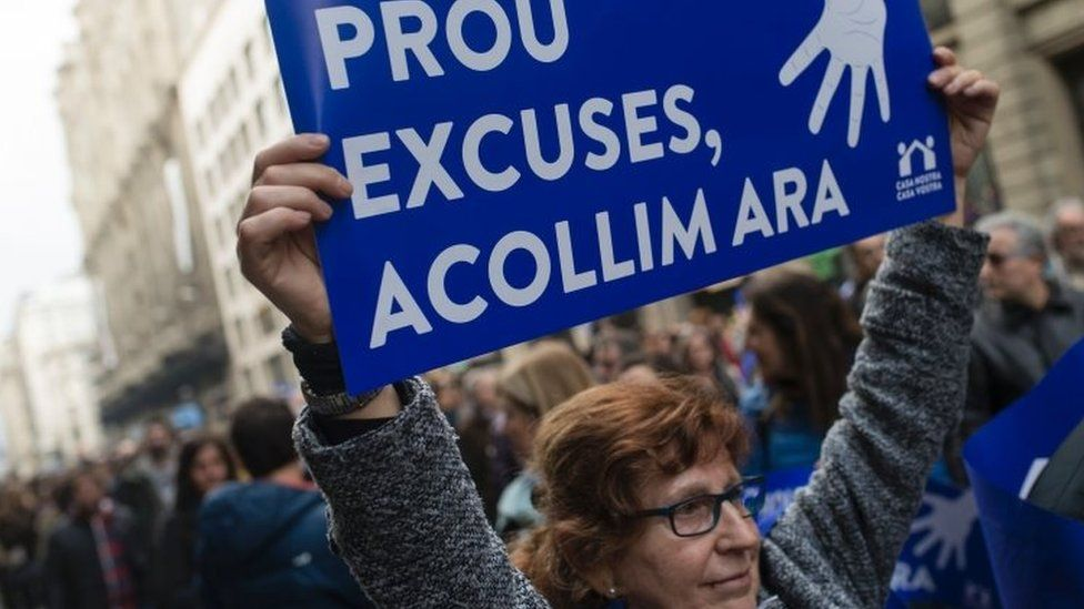 "A woman holds a placard reading ""Enough excuses! Let's welcome now"" during the Barcelona demonstration (18 February 2017)"