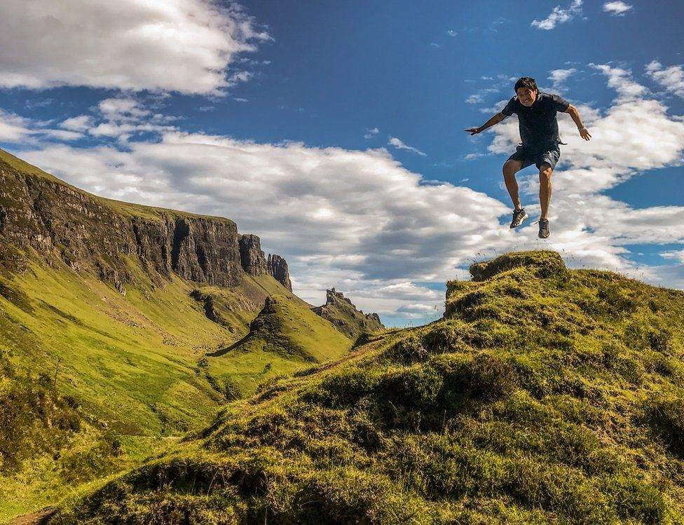 A man jumps while on top of a hill