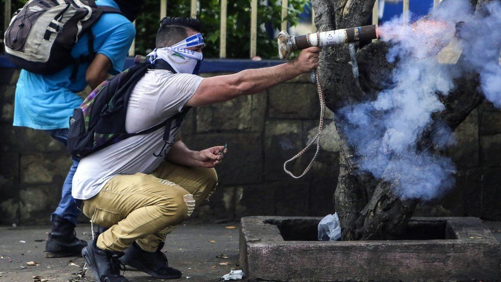 A protester fires a homemade mortar during clashes with riot police. The small welded tubes are hand-held