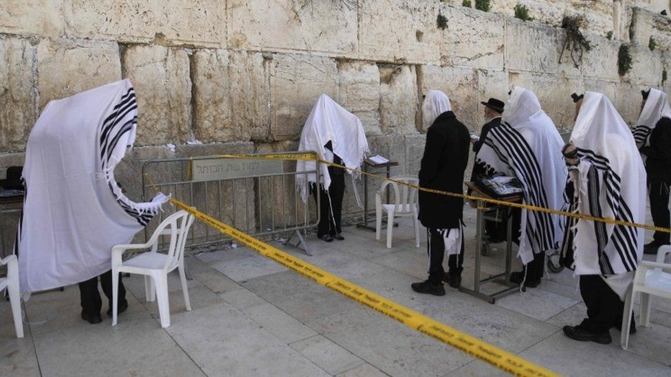 People pray take precautions against the coronavirus while praying at the Western Wall in Jerusalem's Old City (23 March 2020) AFP