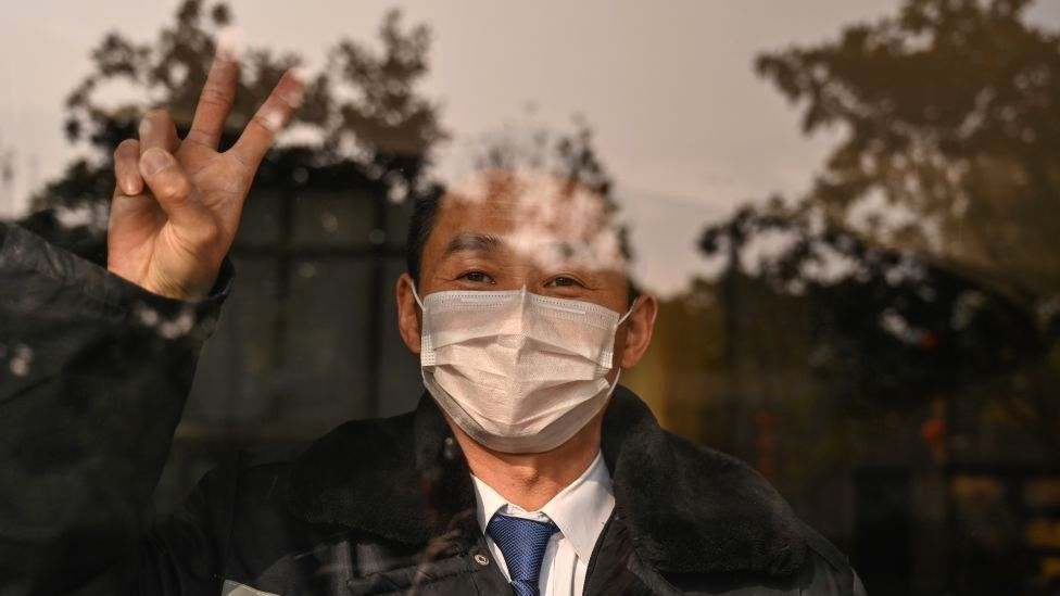 A hotel guard gestures while looking at the camera in Wuhan in China's central Hubei province