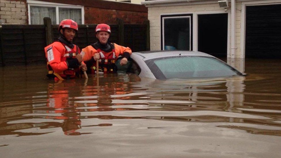 Fire rescue crew beside submerged car in Romford