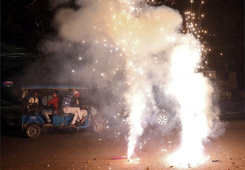 Men travel in a trishaw as firecrackers burn on a street during Diwali, the Hindu festival of lights, in New Delhi, India, November 7, 2018