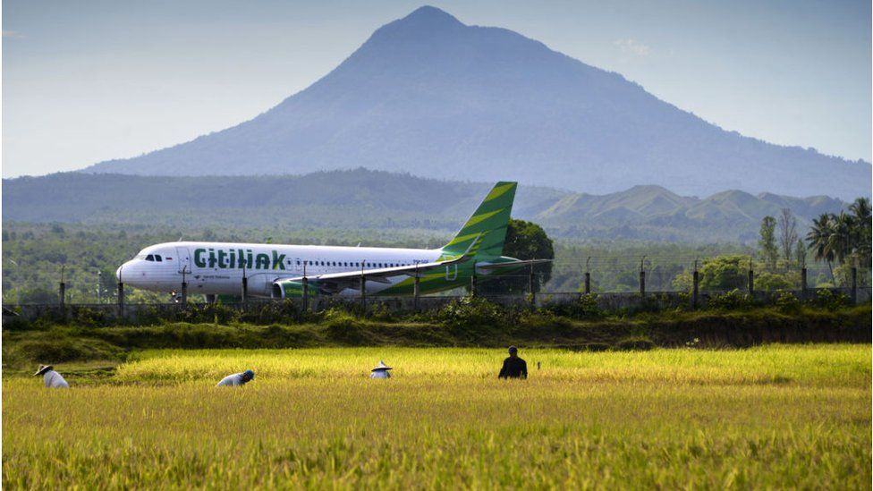A plane taking off from an airport in Indonesia