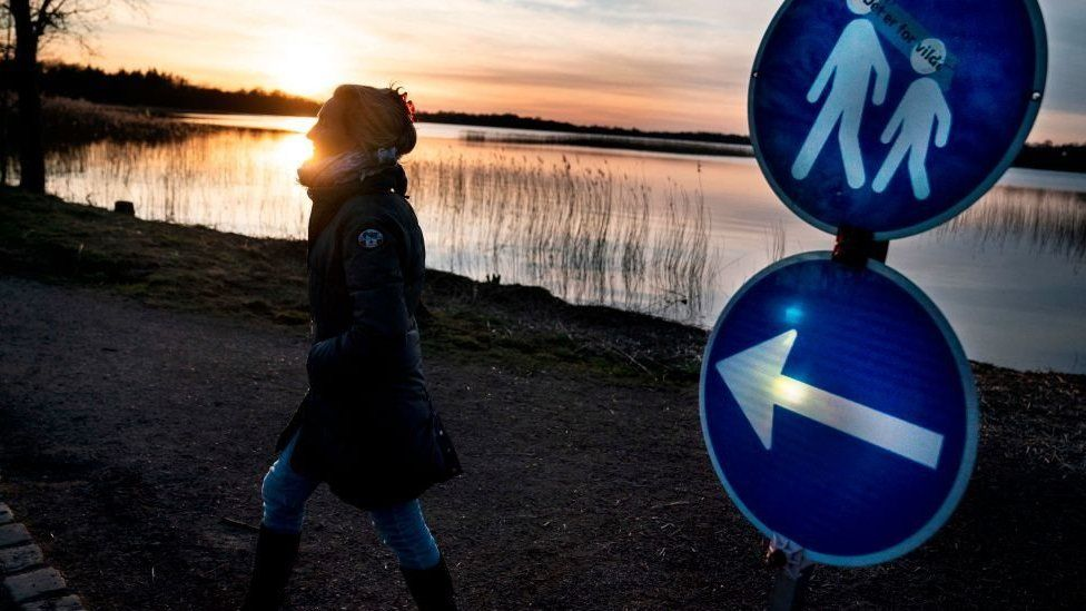 A woman walks on path in Copenhagen where a sign shows that a one-way system is in place