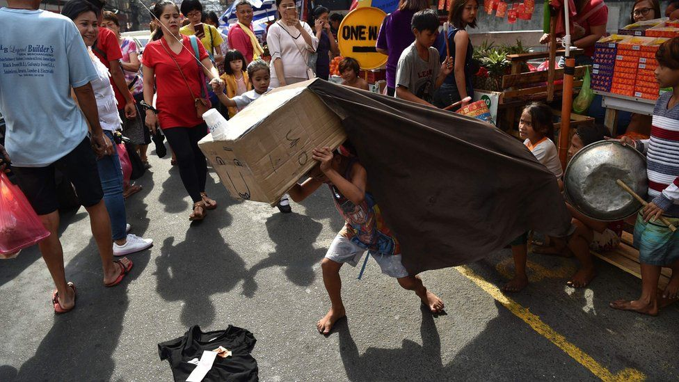 Children perform a lion dance routine with an improvised lion head made from cardboard for pedestrians in the Chinatown district of Manila