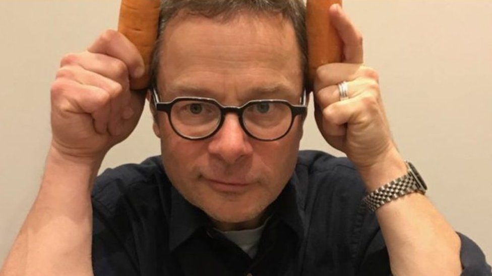 Hugh Fearnley-Whittingstall holding carrots to his head.