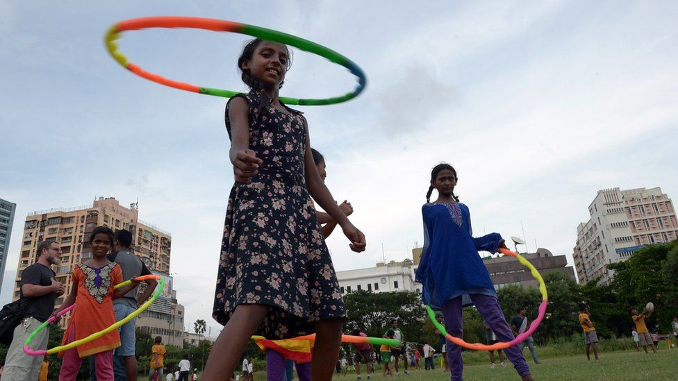Street children play with hula hoops as others play a game with members of the British rugby team Harlequins F.C. in Kolkata on June 16, 2015.