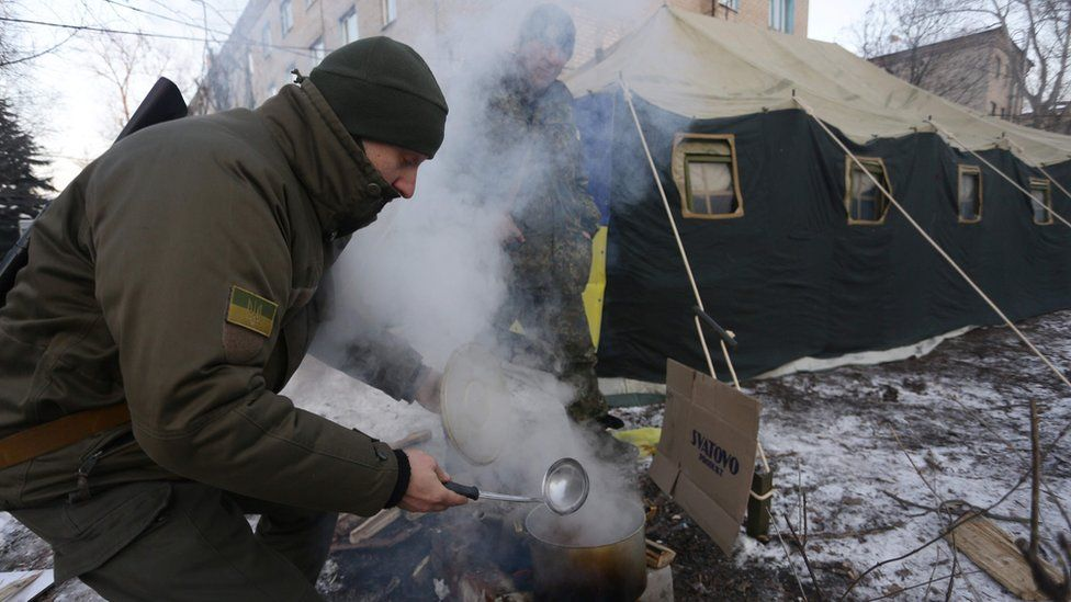 Ukrainian servicemen cook near a tent set to warm local residents of Avdiivka in the Donetsk region after the town's heating was damaged by shells on 31 January 2017.