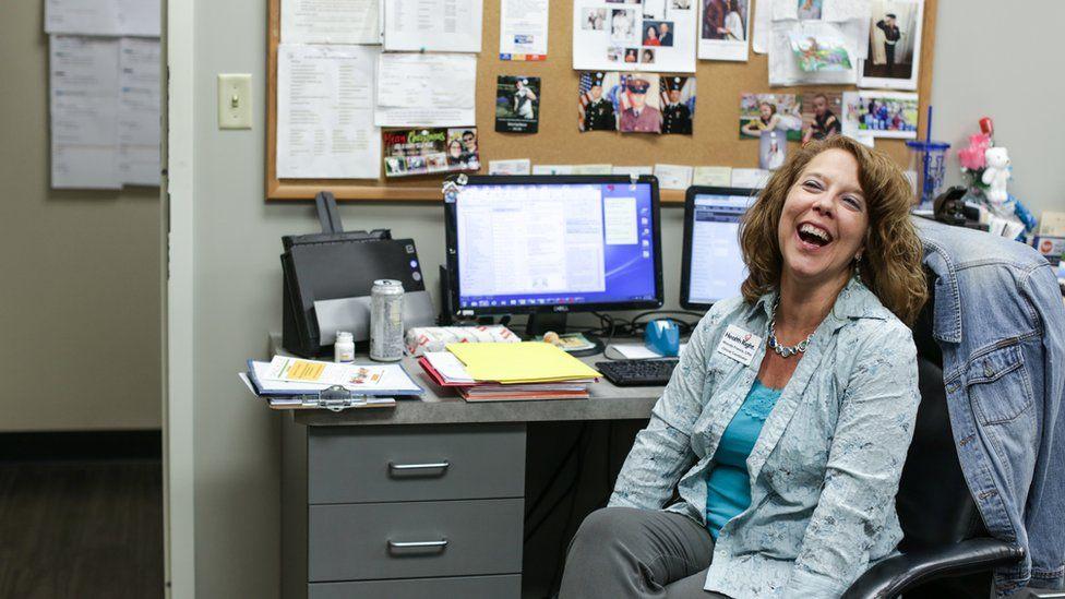 Rhonda Francis at her desk, smiling