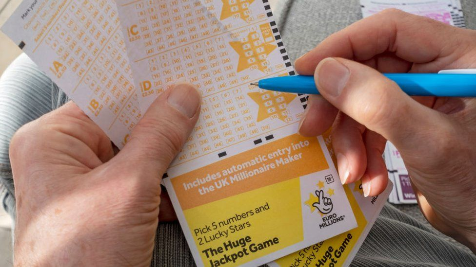 Man filling out EuroMillions lottery ticket