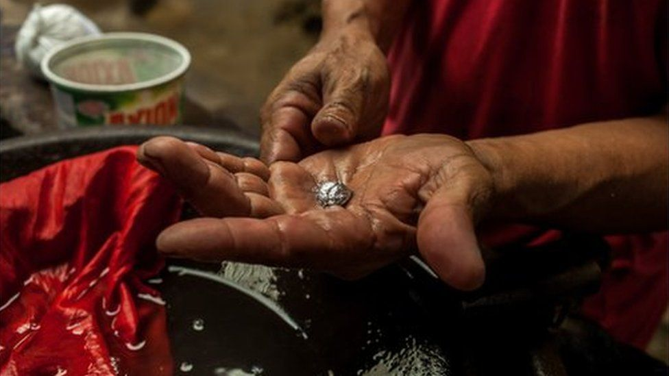 A miner holds a piece of gold in his hand, still chemically bonded to mercury