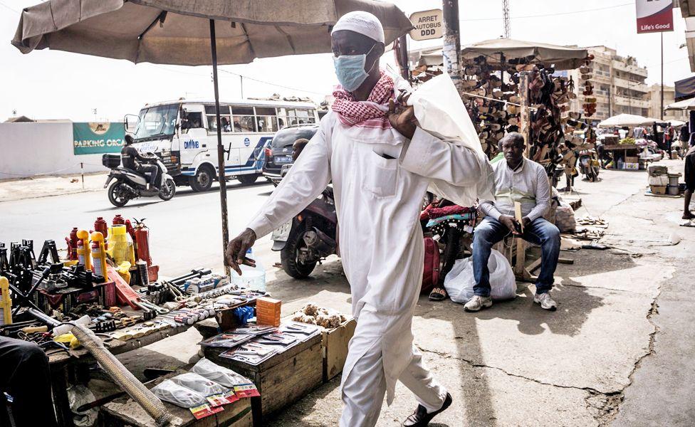A man walks down a street wearing a face mask in Dakar, Senegal - Wednesday 18 March 2020