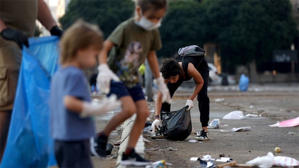 Children help clear rubbish at the site of an anti-government protest in downtown Beirut (21 October 2019)