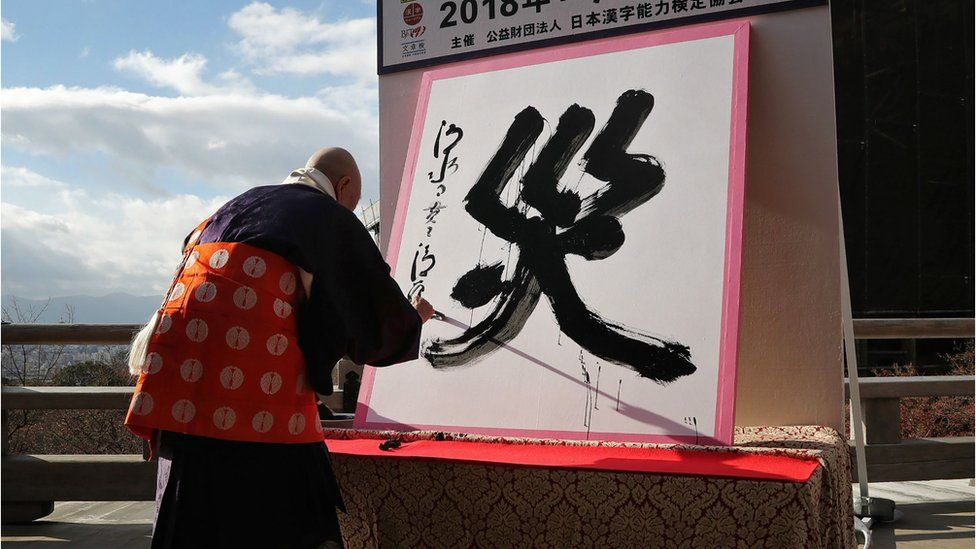 """The kanji character for """"disaster"""", written on a white placard"""