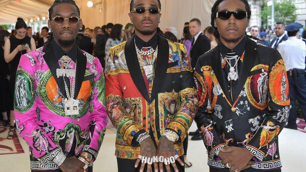 Takeoff, Offset, and Quavo of American hip hop trio Migos arrive in vibrant tuxedos.