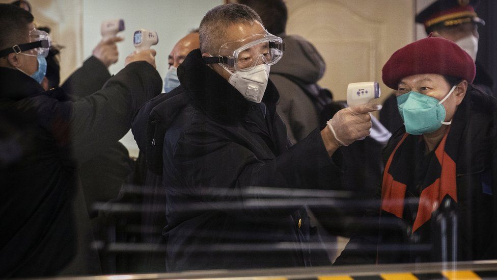 Passengers disembarked from bullet train from Wuhan are checked by health workers at a Beijing railway station