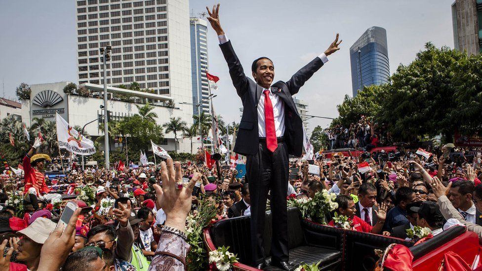 Indonesian President Joko Widodo waves to the crowd while on his journey to the Presidential Palace by carriage during the ceremonial parade on 20 October 2014 in Jakarta, Indonesia.