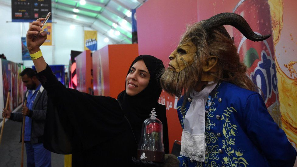 A Saudi woman takes a selfie with person dressed as the Beast from Disney's 2017 Beauty And The Beast film at a Comic Con Arabia event Riyadh on 25 November 2017