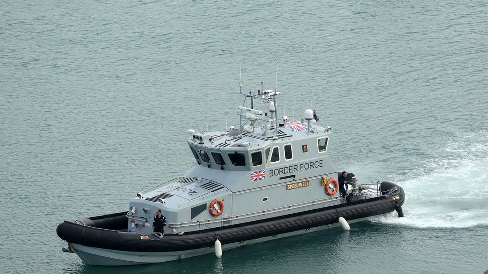 Nine men have been detained after being found in a small boat