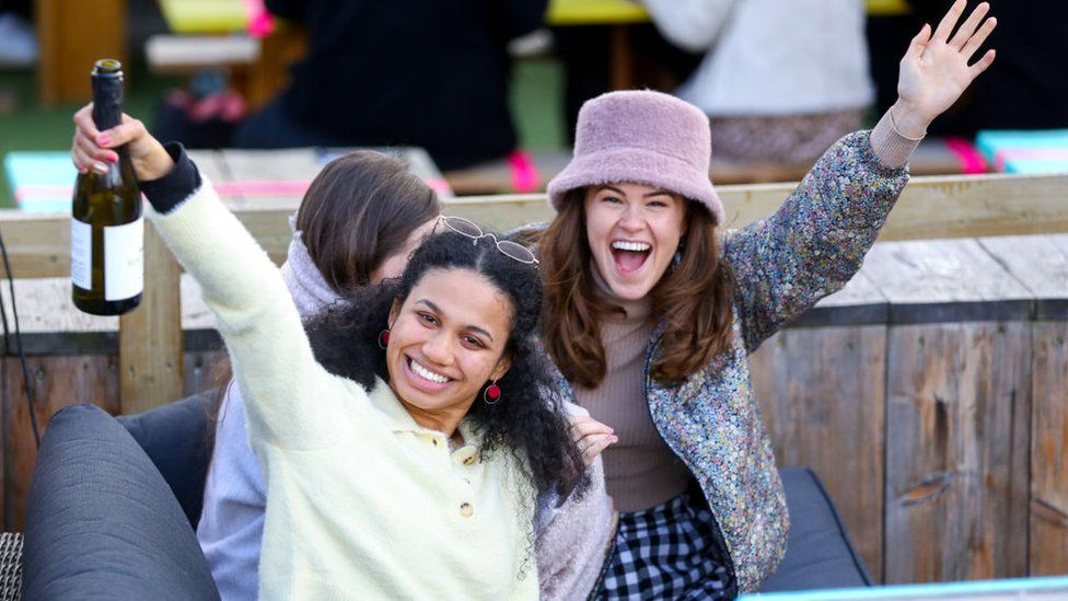 Two friends enjoy a celebratory drink at The Skylight roof top bar in London